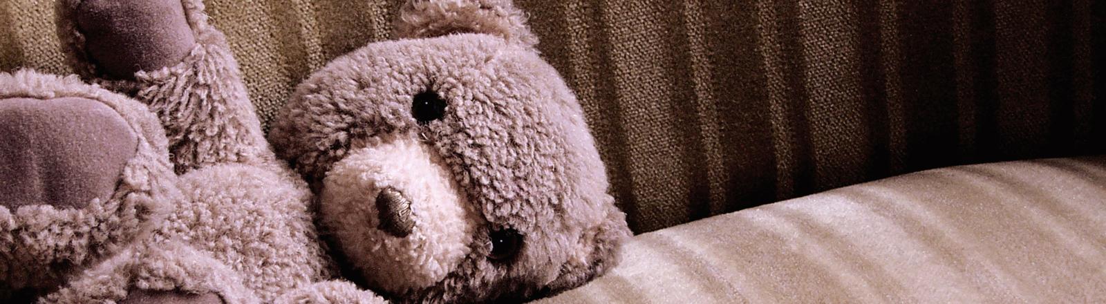 Ein Teddybär, der auf einem altmodischen braunen Sofa liegt.