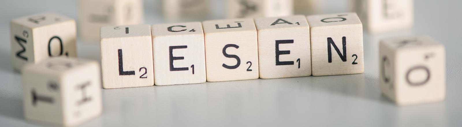 Spielsteine von einem Scrabble-Spiel, die das Wort Lesen ergeben
