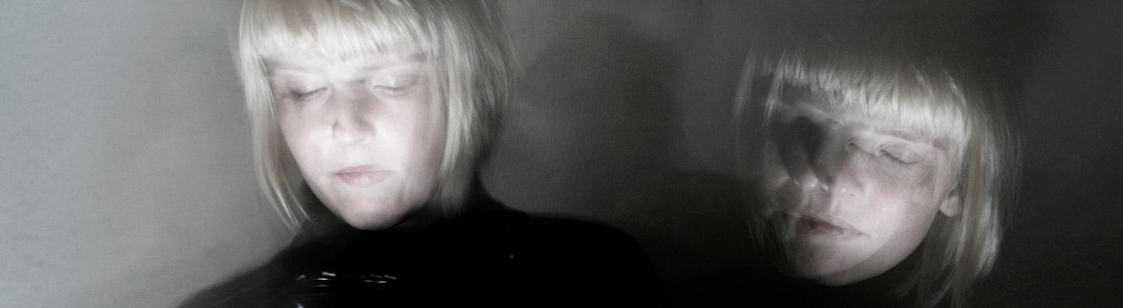 Doppelbelichtung einer Frau, leicht unscharf und in schwarz-weiß.