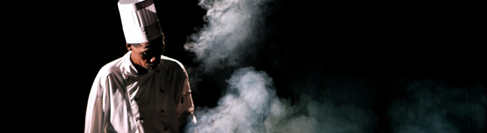 Ein Koch im Halbdunkel steht vor einer Reihe aus dampfenden Kochtöpfen
