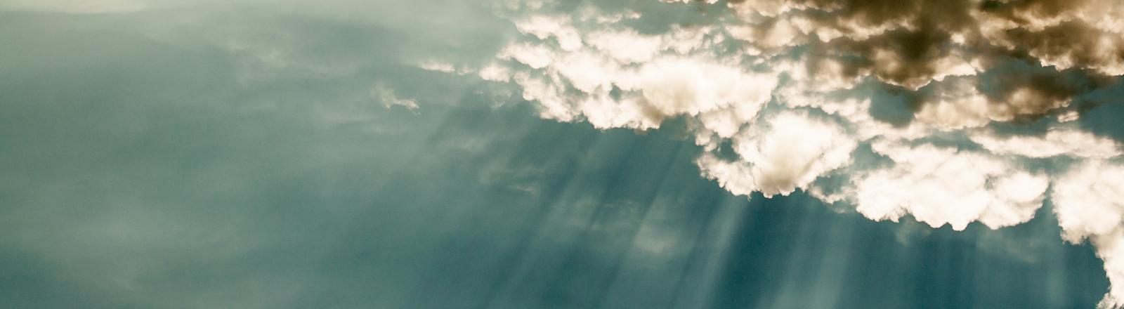 Wolken vor blauem Himmel mit spektakulärem Licht der Sonnenstrahlen.