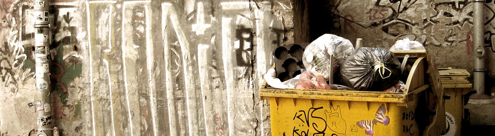 Überfüllter Mülleimer in eimem Hinterhof