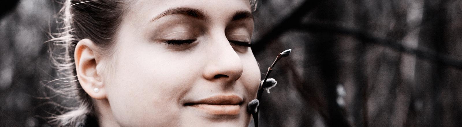 Frau, die an einem Zweig riecht