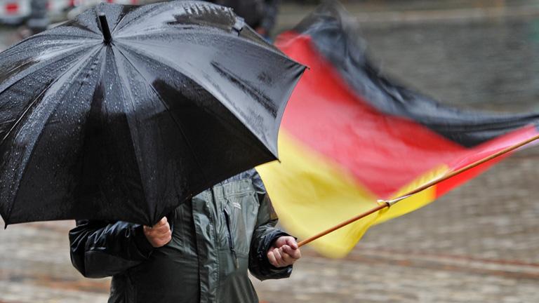 Pegida-Anhänger mit Regenschirm und Deutschlandfahne in Dresden