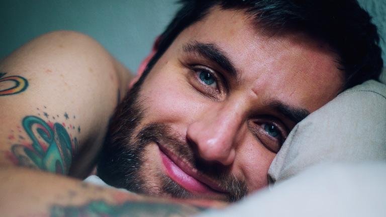 Ein Mann mit Tattoos liegt im Bett und lächelt.