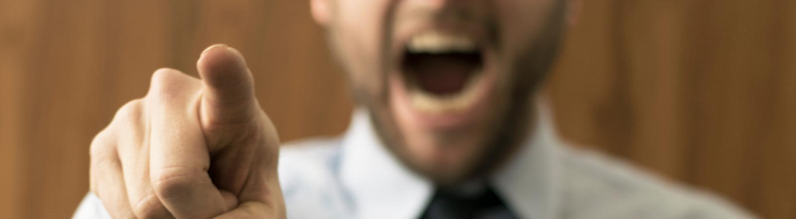 Ein Mann zeigt mit einem Finger auf etwas und reißt den Mund auf.