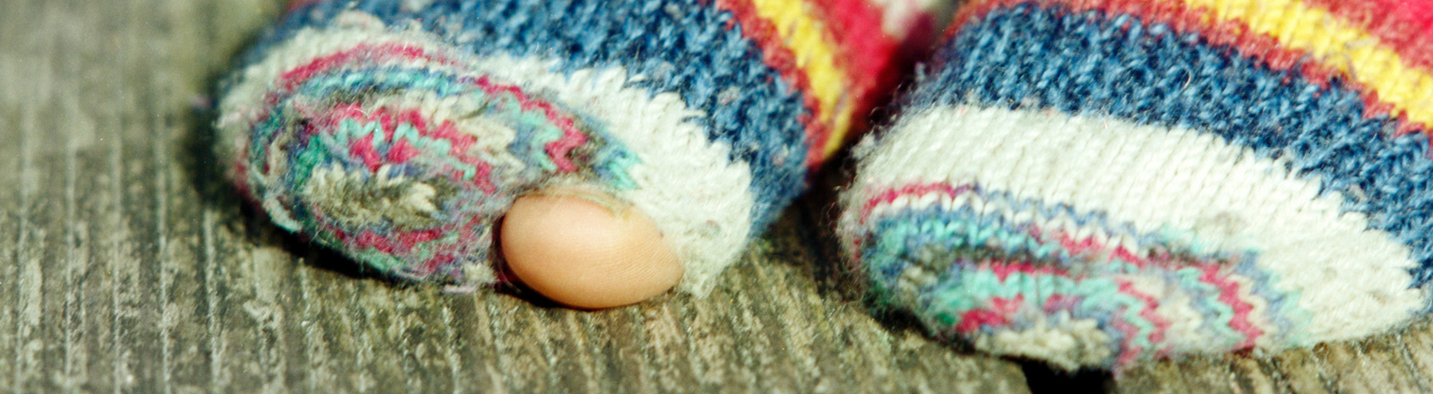 Ein großer Zeh schaut durch ein Loch in einer Socke nach draußen