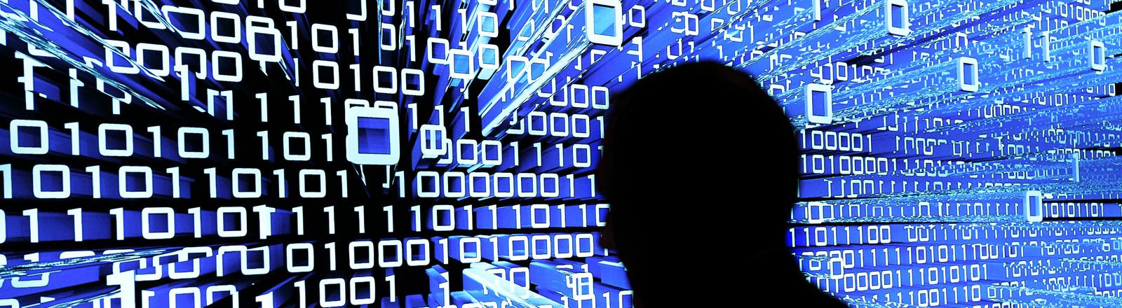 Ein Menschen-Kopf im Schattenriss vor einer Leuchtwand mit Binärcode
