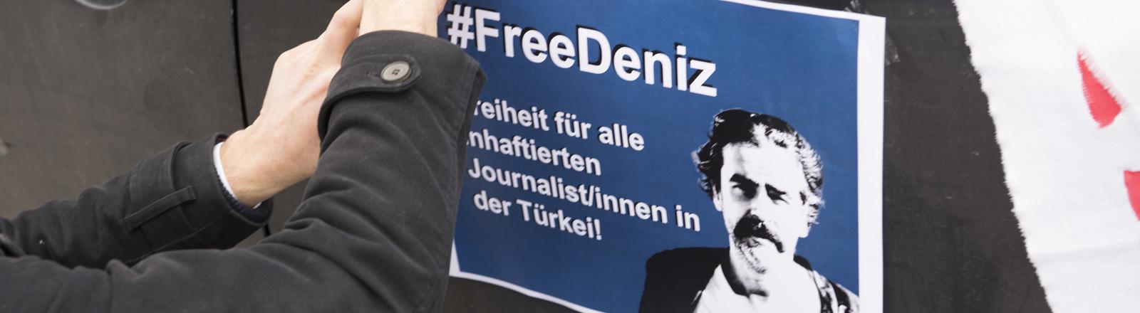 Ein Protestplakat mit dem Hashtag #FreeDeniz wird befestigt