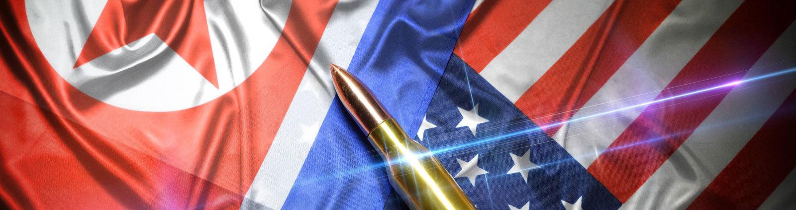 Eine Gewehrpatrone liegt auf den Flaggen Nordkoreas und der USA