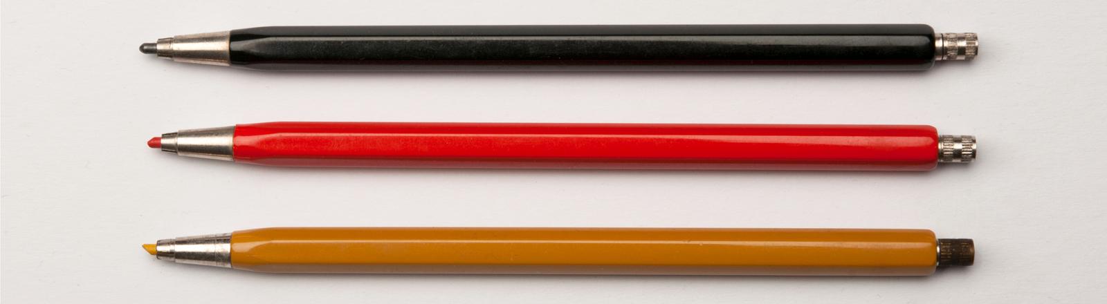 Ordentlich aufgereihte Kugelschreiben in Deutschlandfarben