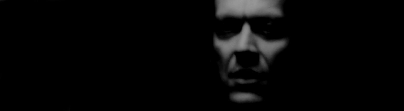 Das unscharfe Gesicht eines Mannes in schwarz/weiß