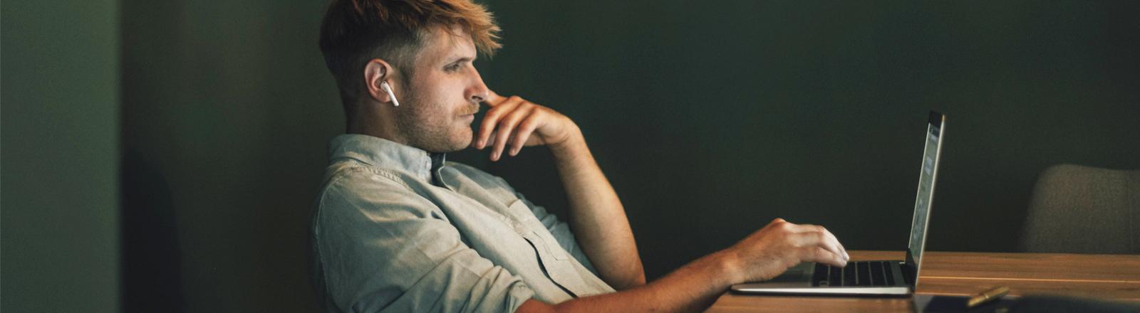 Mann sitzt schief am Laptop
