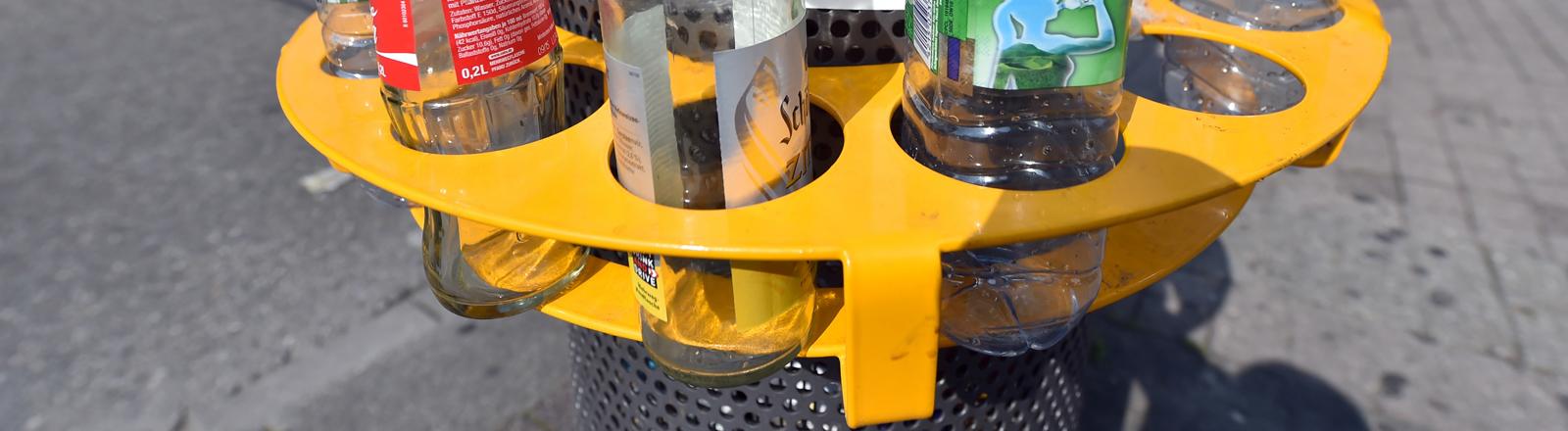 Pfandring, der um einen Mülleimer im öffentlichen Raum hängt.