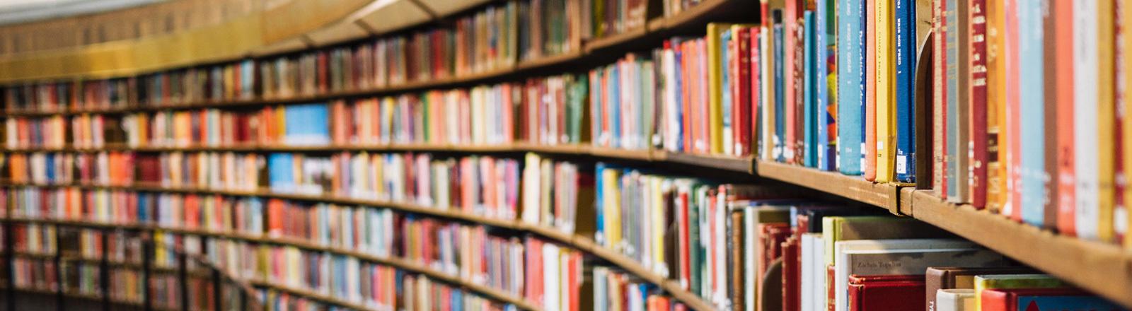 Ein langgezogenes Buchregal in einer Bibliothek.