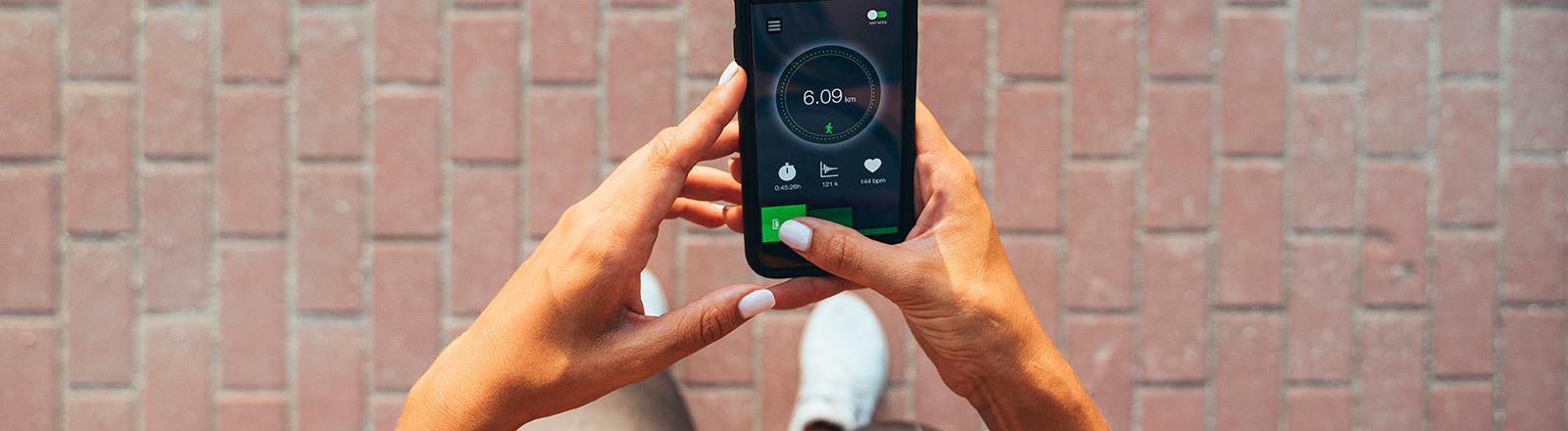 Ein Smartphone wird von zwei Händen gehalten