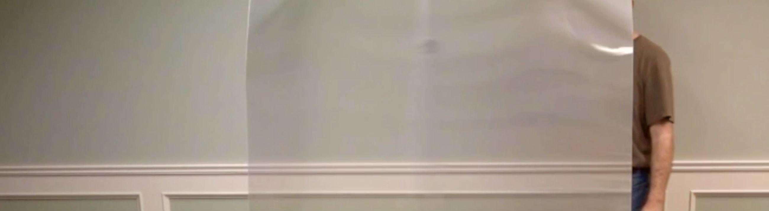 Der Unsichtbarkeitsumhang vor einer Wand. Der Mann dahinter ist komplett verschwunden. Die Wand dahinter ist aber zu sehen.