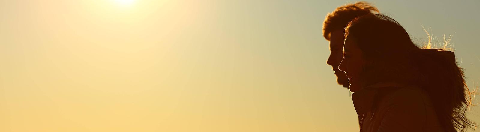Ein Mann und eine Frau im Profil gucken im Sonnenuntergang aufs Meer.