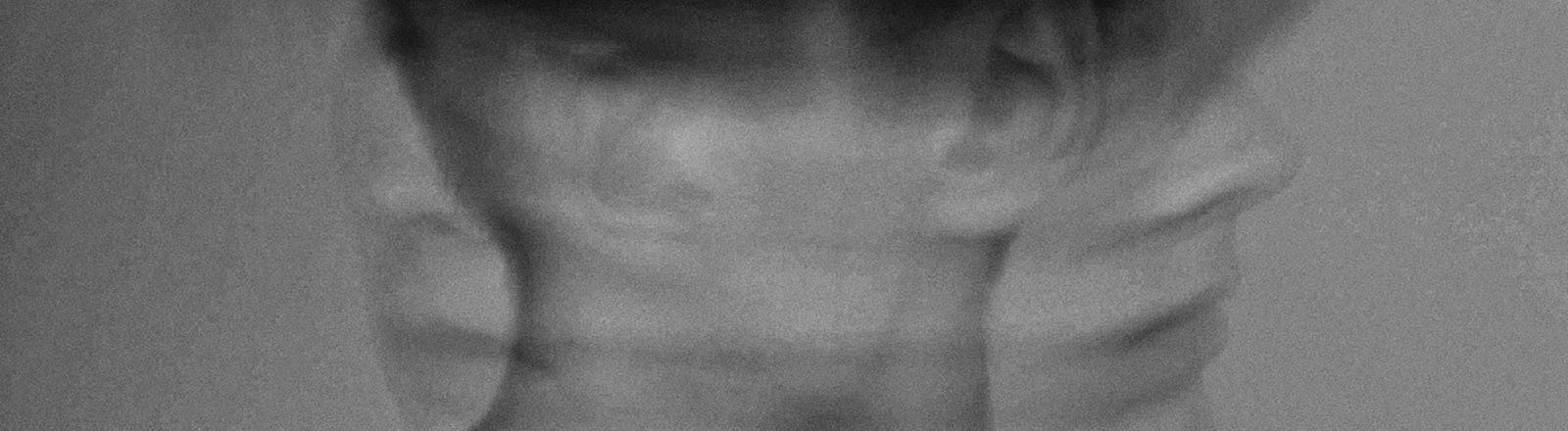 Ein Mann dreht den Kopf schnell nach links und rechts. Das Foto ist unscharf. Es wirkt konfus.
