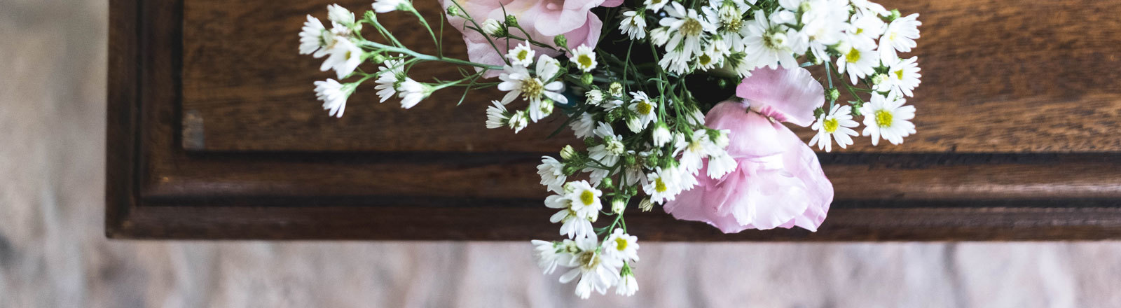 Ein Holzsarg auf dem ein Blumenstrauß steht.