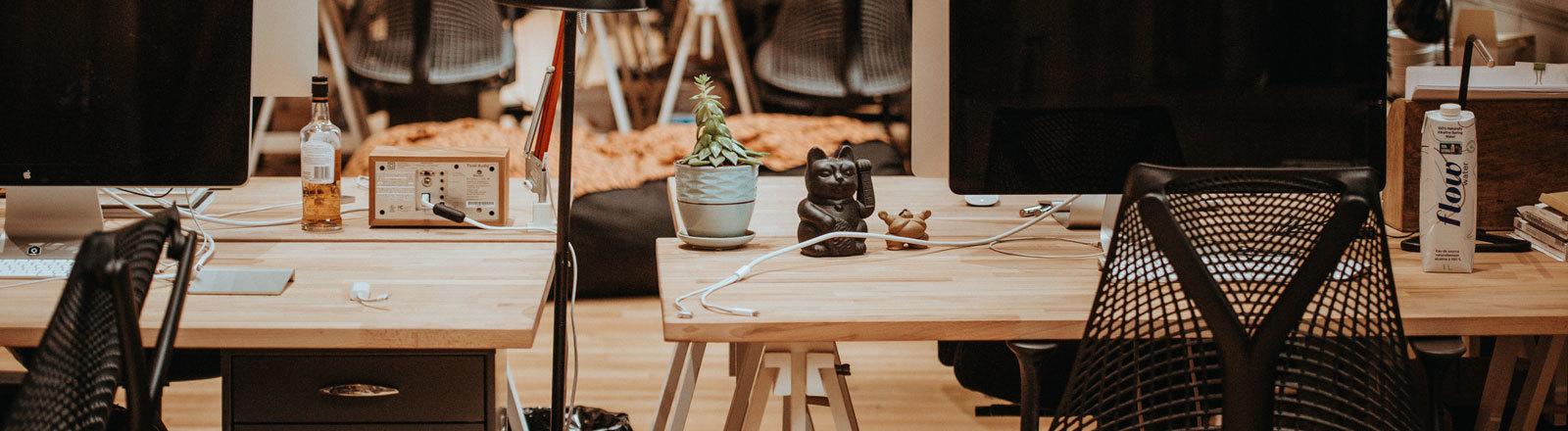 Schreibtische aus Holz mit Stühlen davor und Bildschirmen darauf.