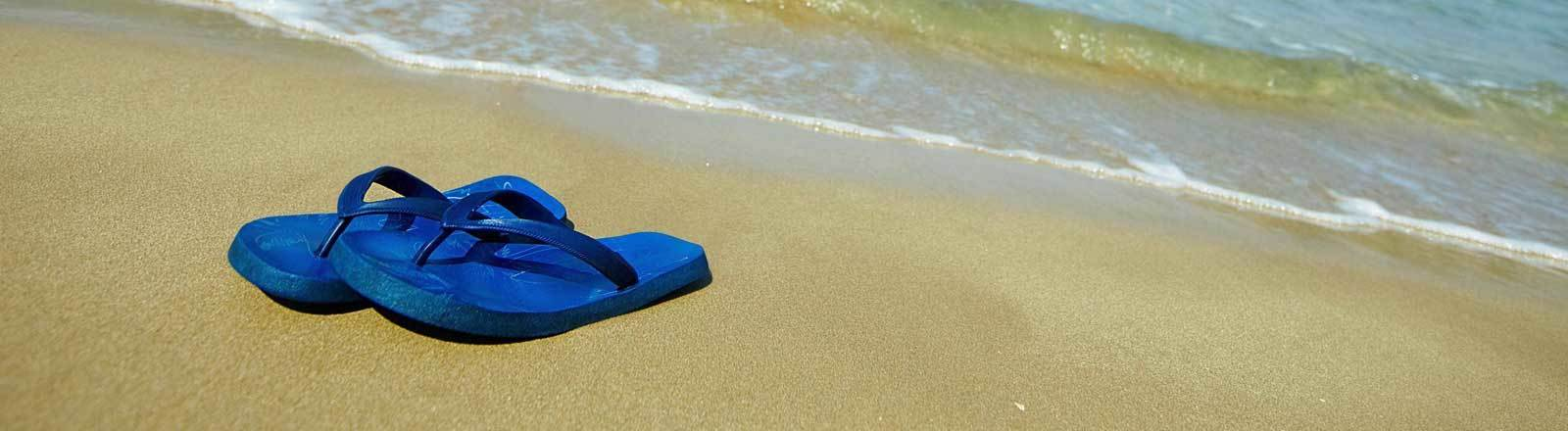 Ein Paar blaue Flipflops liegen an einem Sandstrand