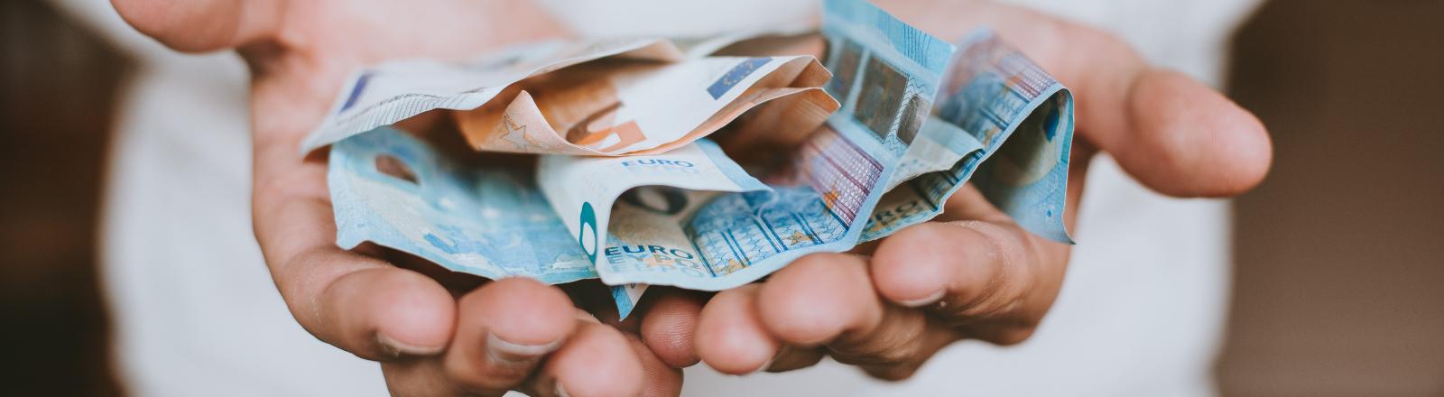 Eine Person hält Geldscheine in ihren Händen.