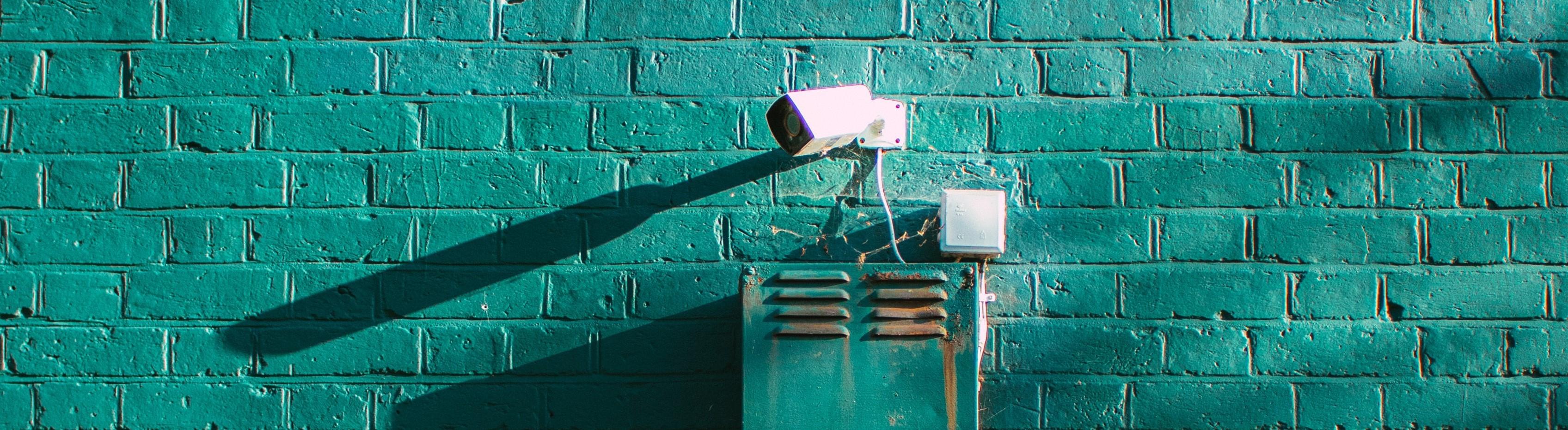 Überwachungskamera hängt an türkiser Wand