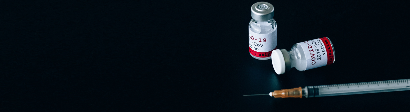 Eine Spritze liegt neben zwei Impfdosen.