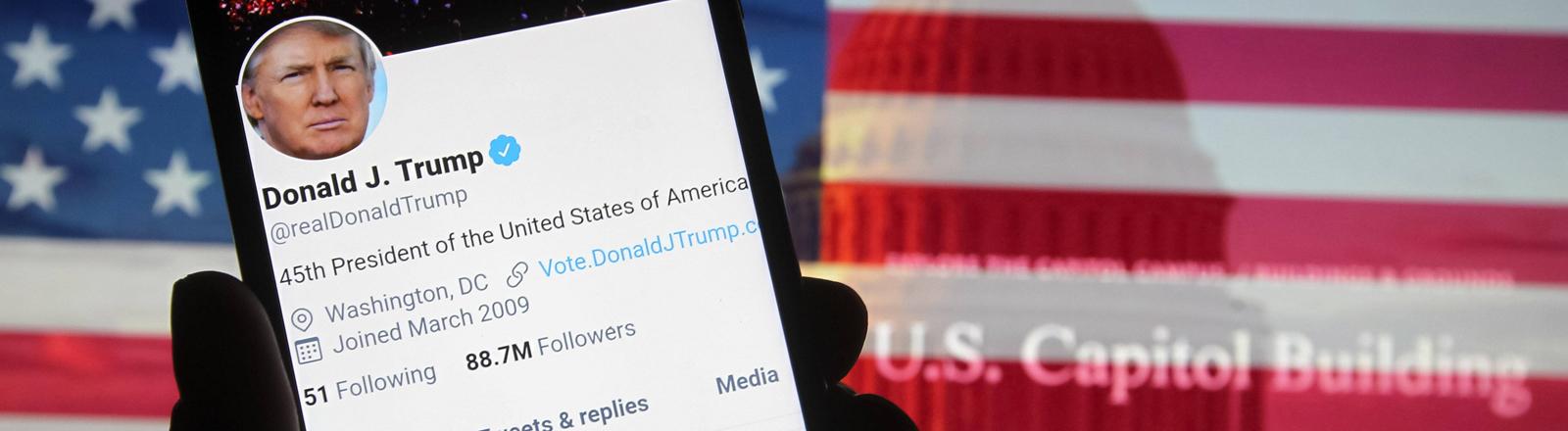 Ein Handy mit dem Twitter-Account von Donald Trump vor der US-Flagge.