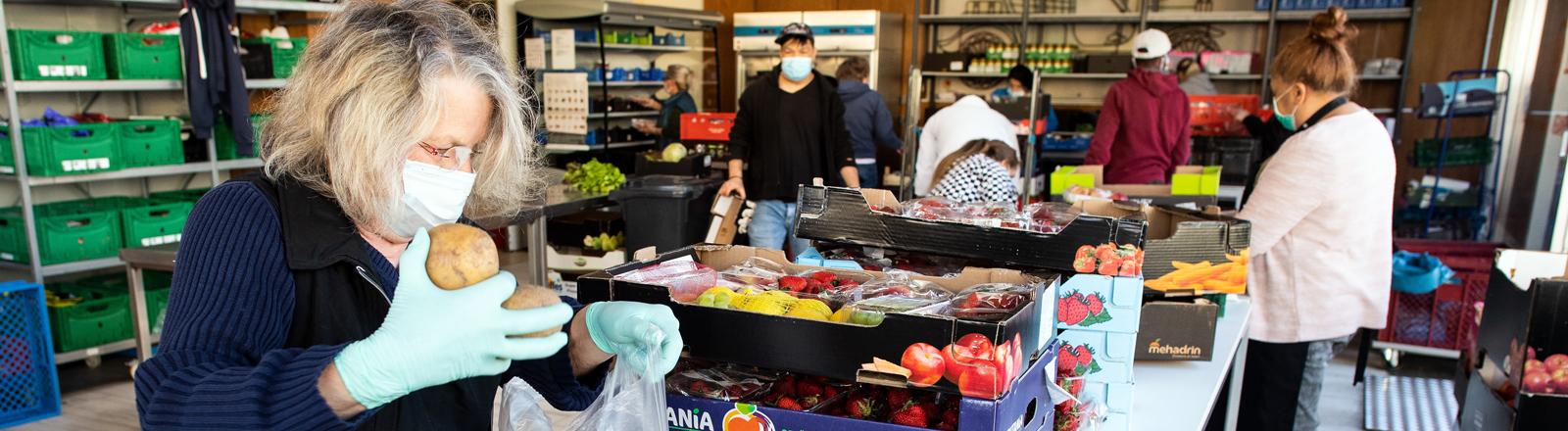 In einer der Tafeln Deutschlands werden Lebensmittel eingepackt.
