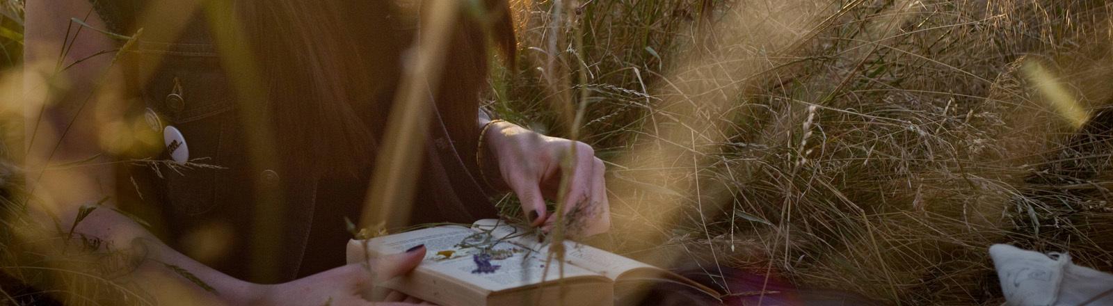 Mädchen liegt mit Buch im Gras
