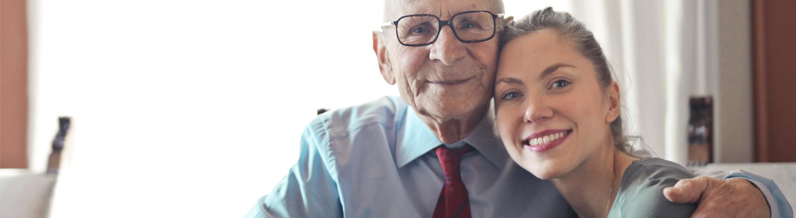 Ein alter Mann hat den Arm um eine jüngere Frau gelegt.