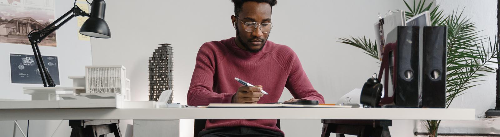 Ein Mann sitzt am Schreibtisch und arbeitet.