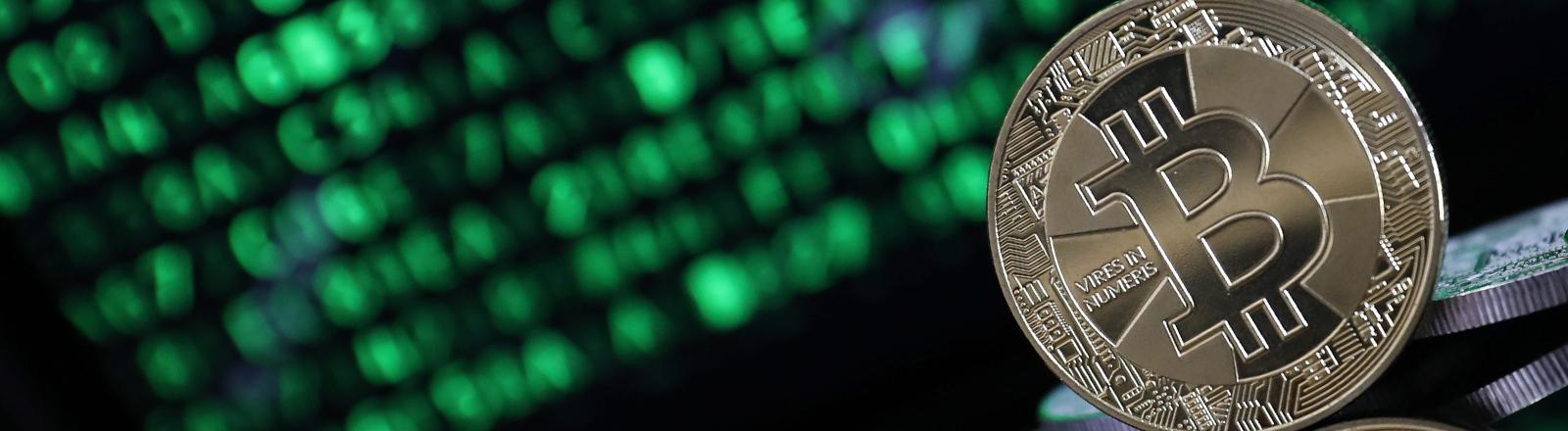 Ein Bitcoin vor einem Computermonitor.