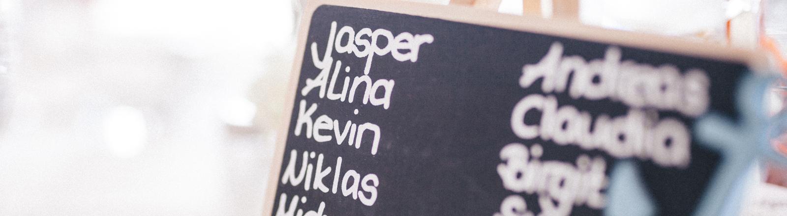 Auf einer Kreidetafel stehen verschiedene Namen.