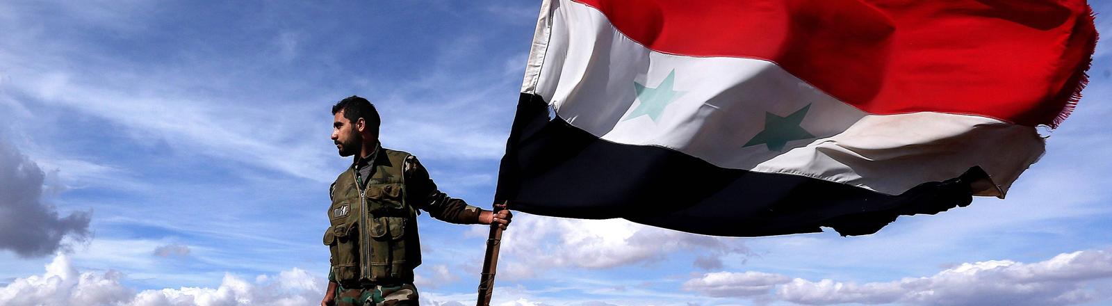 Ein Soldat der syrischen Regierung mit der Nationalflagge.