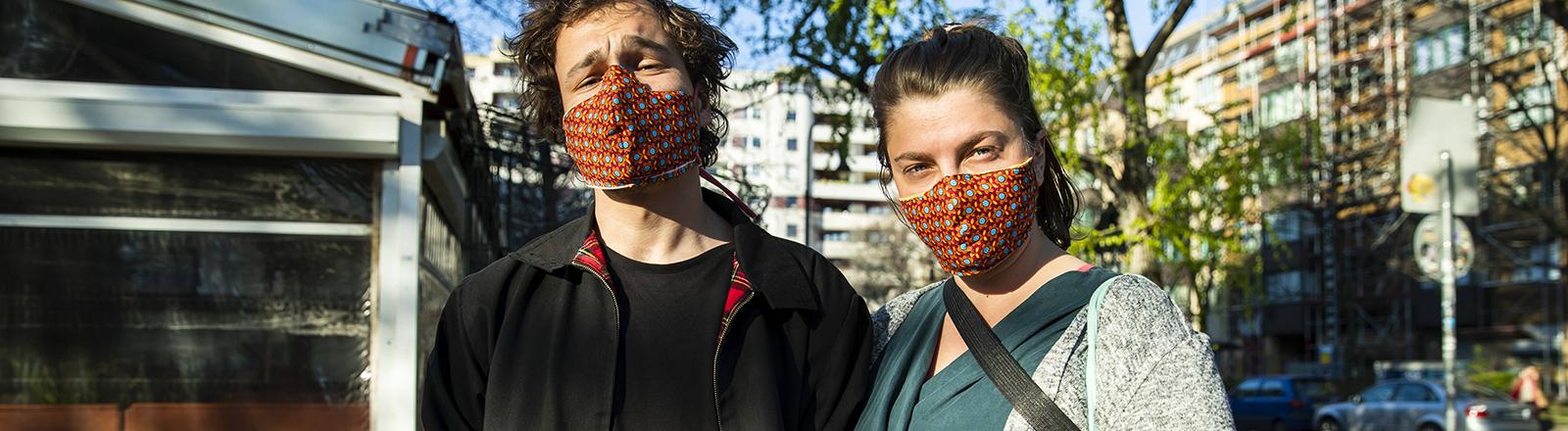 Zwei Personen mit Mund-Nase-Masken schauen in die Kamera.