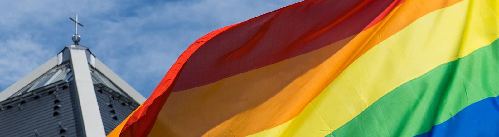 Die Regenbogenfahne weht vor einer katholischen Kirche.