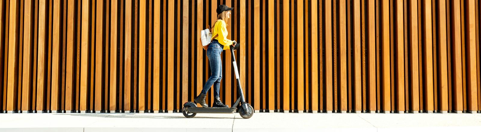 Eine Frau fährt E-Scooter.
