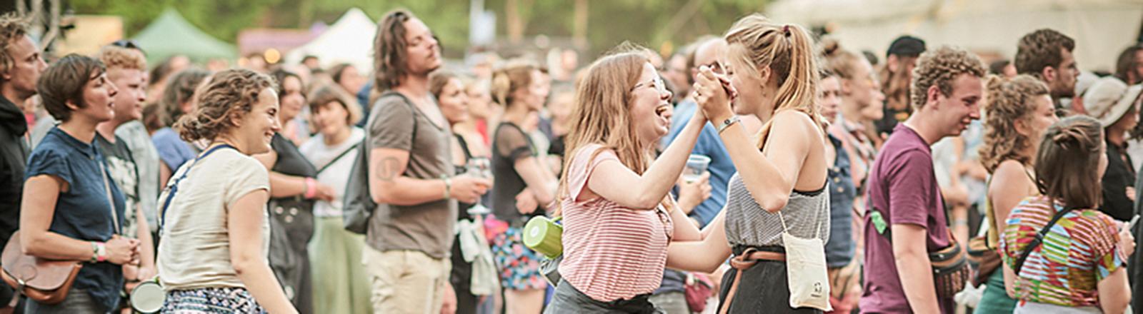 In einer Menschenmenge tanzen zwei Frauen.