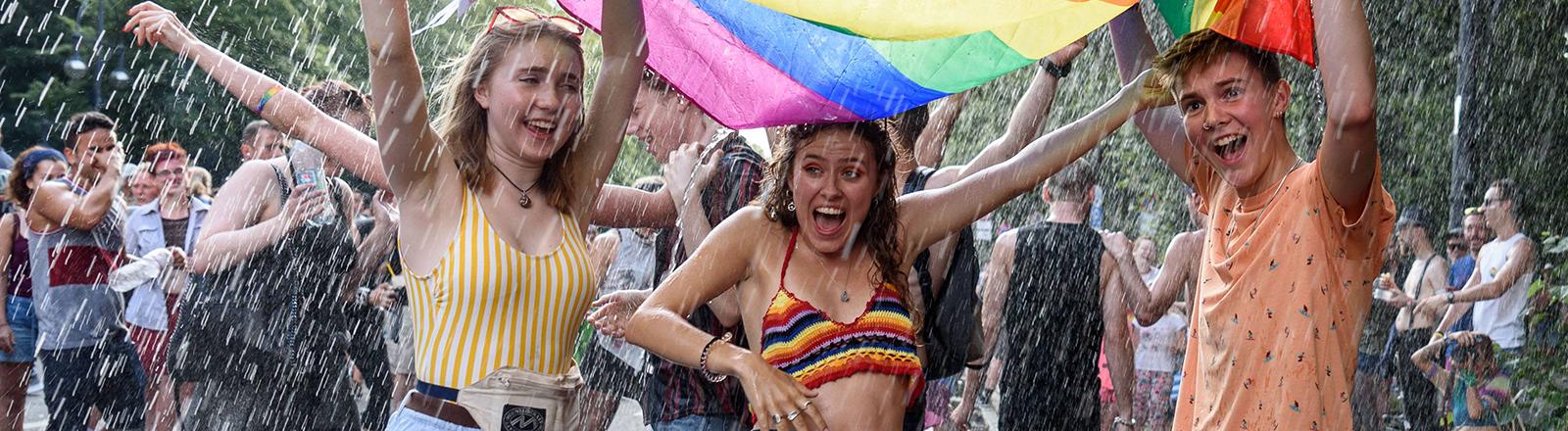 Drei Personen stehen unter einer Regenbogenflagge und sie werden mit Wasser bespritzt.