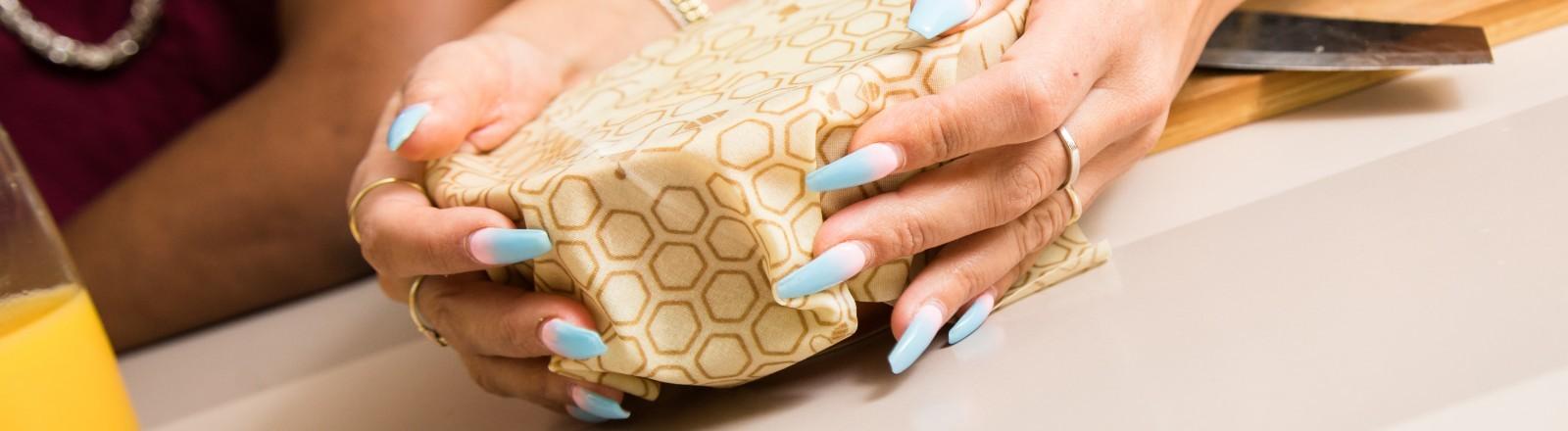 Eine Frau schließt eine Schüssel mit Bienenwachstuch