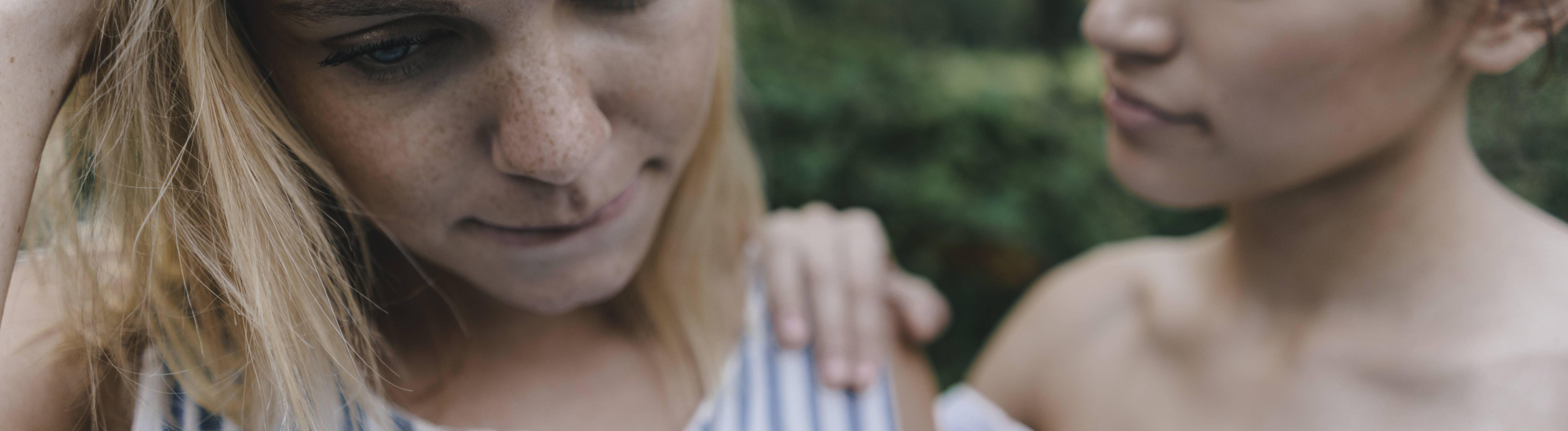 Zwei Frauen stehen nebeneinander. Die eine schaut sie Boden, die andere legt ihr die Hand auf die Schulter.