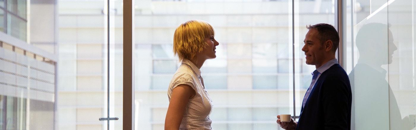Eine Kollegin unterhält sich konzentriert mit einem Kollegen