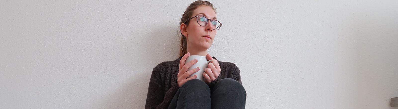 Eine Frau sitzt auf dem Fußboden und hält eine Tasse in der Hand