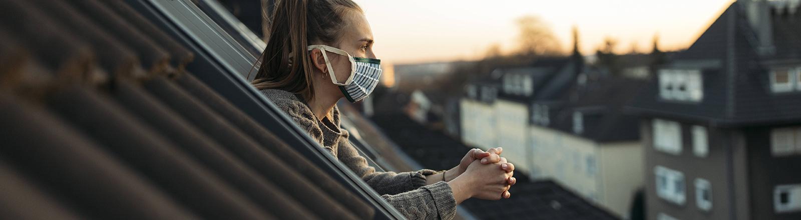 Eine Frau trägt einen Mund-Nasen-Schutz an einem offenen Fenster und hat die Hände gefaltet.