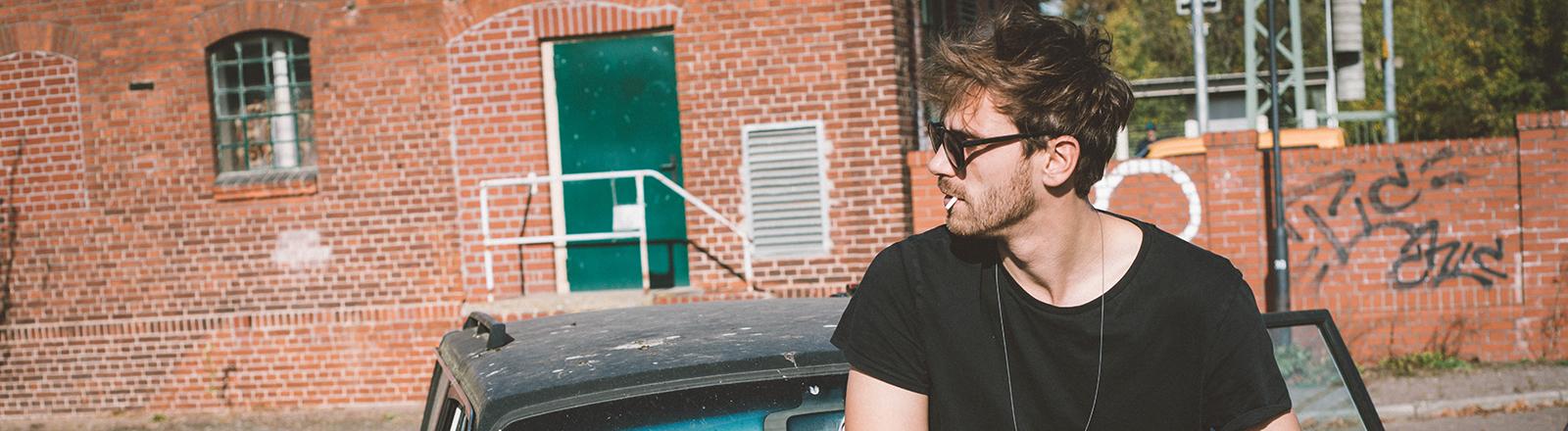 Eine Mann sitzt auf einem Auto und dreht sich eine Zigarette.