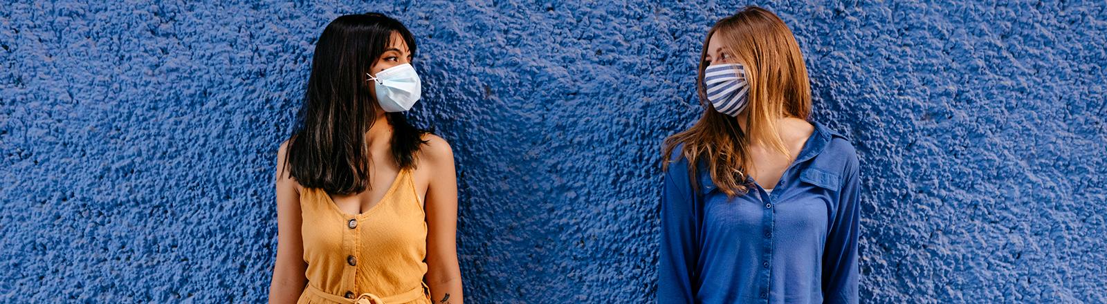 Zwei weiblich gelesene Personen tragen einen Mund-Nase-Schutz und schauen sich an.