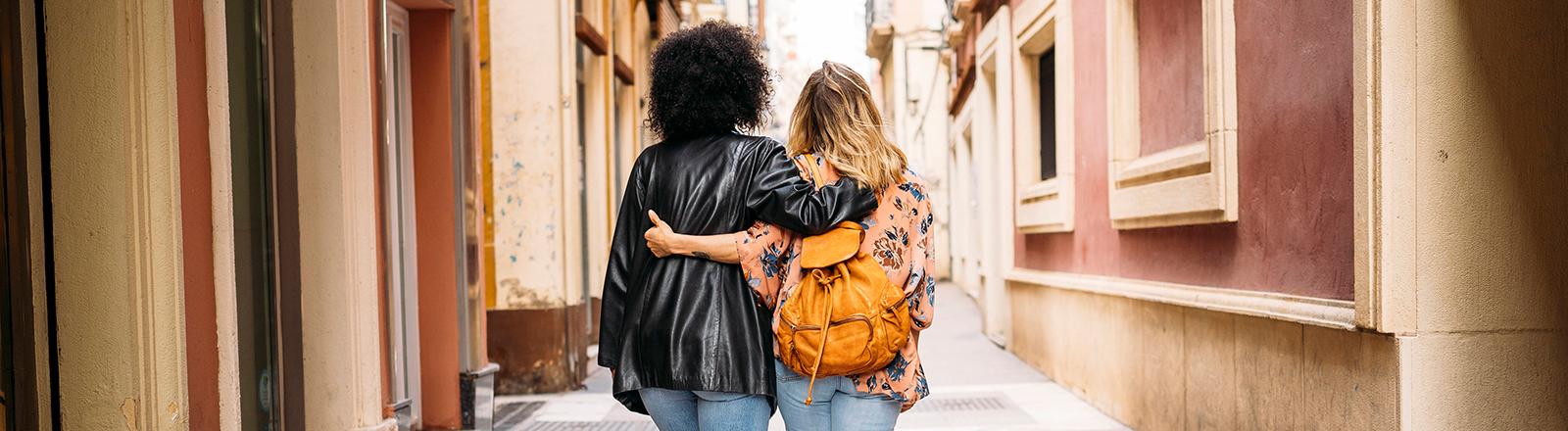 Zwei weiblich gelesene Personen gehen Arm in Arm eine Straße entlang.